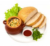 stock photo of pot roast  - roast with greens sauce bread and tomato in a brown clay pot - JPG