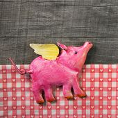 Flying happy pink pig on wooden old checked background. Symbol for happiness and luck.