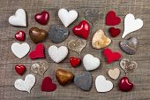 Collection of different red, white and brown hearts on wooden background for decoration. Idea for christmas, new year, valentine or friendship.