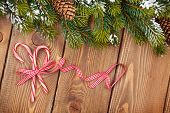 Christmas wooden background with snow fir tree and candy canes
