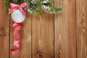 Christmas fir tree and bauble with red ribbon on rustic wooden board with copy space