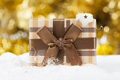Golden Christmas background with snow, Christmas ball and gift box