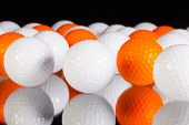 White And Orange Golf Balls On The Glass Table