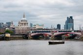 Small Vintage Fishing Boat Passing Arch Bridge at Famous River Thames in London, with St Paul Cathedral View Afar.