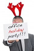 a man in suit with a reindeer antlers headband holding a signboard with the text office holiday party written in it