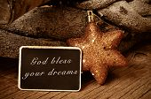 the text god bless your dreams written in a blackboard and a christmas star and a pile of logs in the background