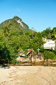 Rustic buildings and a church on Port Launay South beach in Seychelles set in lush tropical vegetation