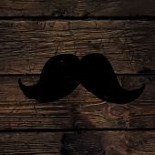 Moustache symbol on wooden texture.