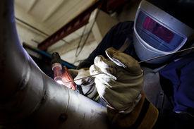 stock photo of pipe-welding  - welder in factory with protective equipment welding metal pipes - JPG