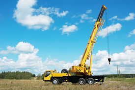 picture of boom-truck  - yellow automobile crane with risen telescopic boom outdoors over blue sky - JPG
