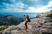 image of mountain-climber  - Young woman mountain climber with backpack and sleeping back hiking on the rocky mountain