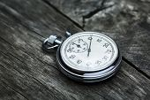 stock photo of stopwatch  - Steel stopwatch on the old textured gray wooden surface - JPG
