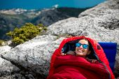 pic of sleeping bag  - Young woman lying in red sleeping bag on the rocky mountain - JPG