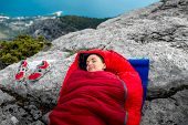 image of sleeping bag  - Young woman sleeping in red sleeping bag on the rocky mountain - JPG