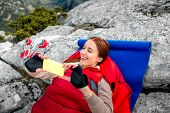 picture of sleeping bag  - Young woman taking selfie photo in red sleeping bag on the rocky mountain - JPG