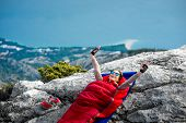 pic of sleeping bag  - Young woman waking up in red sleeping bag on the rocky mountain - JPG