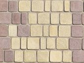 image of trapezoid  - textured paving tiles imitating stone path with rounded edges and seams are covered with fine beige marble chips - JPG