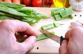 foto of cutting board  - Cook cut green beans for cooking on a cutting board on a kitchen table with vegetables background - JPG