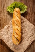 stock photo of butter-lettuce  - Garlic baguette with lettuce on a wooden table.