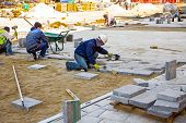 stock photo of paving  - Workers stack paving block on city street