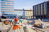 stock photo of geodesic  - Surveying measuring equipment level transit on tripod at construction building area site - JPG