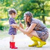 pic of cute kids  - Beautiful young woman and her little cute kid daughter in yellow and red rubber rainboots family look in summer park - JPG