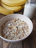 stock photo of porridge  - oat porridge with bananas and yogurt on a wooden table