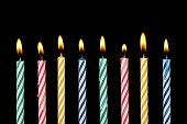 pic of candle flame  - eight colorful birthday candles with flame on black - JPG