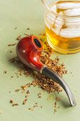 image of tobacco-pipe  - Tobacco pipe on rustic warn green wood surface with spilled natural tobacco and a glass of whisky on the rocks - JPG