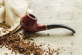 stock photo of tobacco leaf  - Tobacco pipe on rustic warn wood surface with spilled natural tobacco - JPG