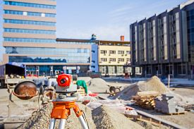 pic of geodesic  - Surveying measuring equipment level transit on tripod at construction building area site - JPG