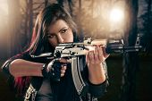 picture of rifle  - Attractive girl in forest standing in the attitude of aiming and looking through the sight automatic rifle - JPG