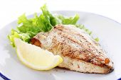 image of plate fish food  - Dish of fish fillet with lettuce and lemon on plate close up - JPG