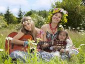 pic of hippy  - Hippie mommy with her daughters sitting on the lawn - JPG
