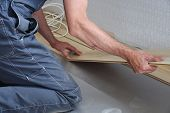 picture of laminate  - hands of a carpenter install laminate in the room - JPG