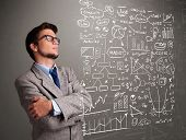 stock photo of anal  - Attractive young man looking at stock market graphs and symbols - JPG