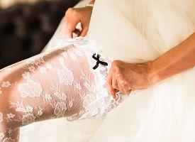 image of garter-belt  - bride dresses garter on the leg - JPG