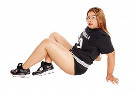 stock photo of snickers  - A young Asian woman in black sports clothing and snickers sitting on the