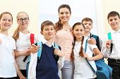 Teacher with children in school corridor during class break poster