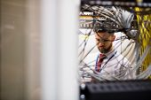 Technician checking cables in a rack mounted server in server room poster