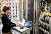 Technician using laptop while analyzing server in server room poster