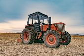 Tractor working on the farm, agricultural transport, a farmer working in the field, tractor at sunse poster