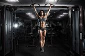 Sexy Young Fitness Girl Pulls Up In The Gym. Brunette Fitness Woman In Black Sport Wear With Perfect poster