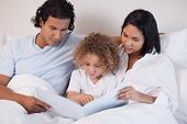 Happy young family enjoys reading a book together