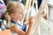 Cute Blond Smiling Girl Painting On Easel In Workshop Lesson At Art Studio. Kid Holding Brush In Han poster