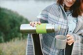 Hands Of Girl With Thermos Pours Hot Tea Into Mug On Meadow On Background Of River At Misty Morning. poster
