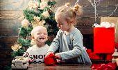 Cute Little Child Near Christmas Tree. Cheerful Cute Child Opening A Christmas Present. Christmas Ki poster