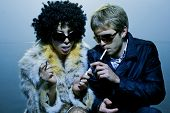Fashionable young couple wearing sunglasses smoke a cigaret