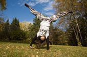 A young woman makes a handstand on grass in front of blue sky