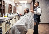 Hipster Man Client Visiting Haidresser And Hairstylist In Barber Shop. poster